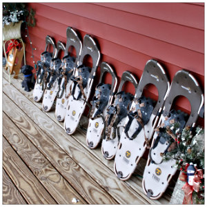 A lineup of snowshoes along a red wall of a house