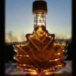 A clear bottle in the shape of a maple leaf filled with maple syrup