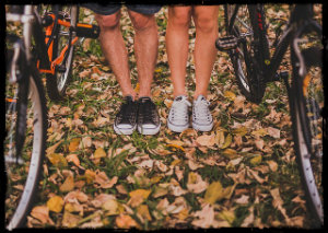 A man and a woman's legs and feet with tennis shoes standing in a wooded area with bikes next to each person