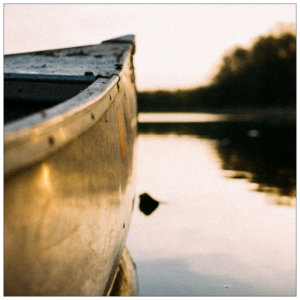 Front tip of a grey canoe on calm water at sunset with trees in the background