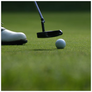 Golfer on a putting green with a putter next to a white golf ball